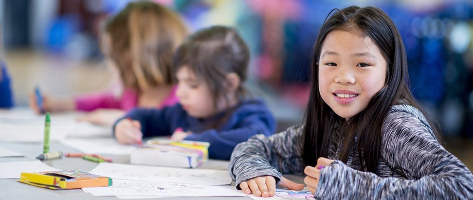 group of elementary age students at school or daycare coloring pictures
