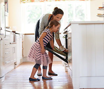 daughter helping mother get pan out of the oven