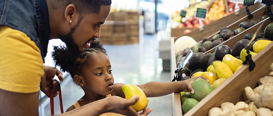 daughter helping father pick out fruit at the grocery store