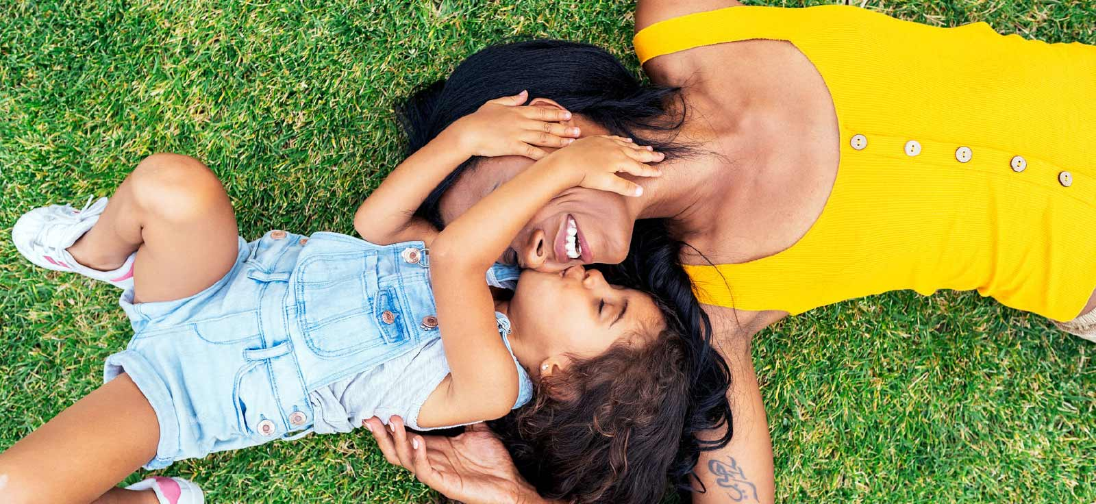mother and daughter playing on grass
