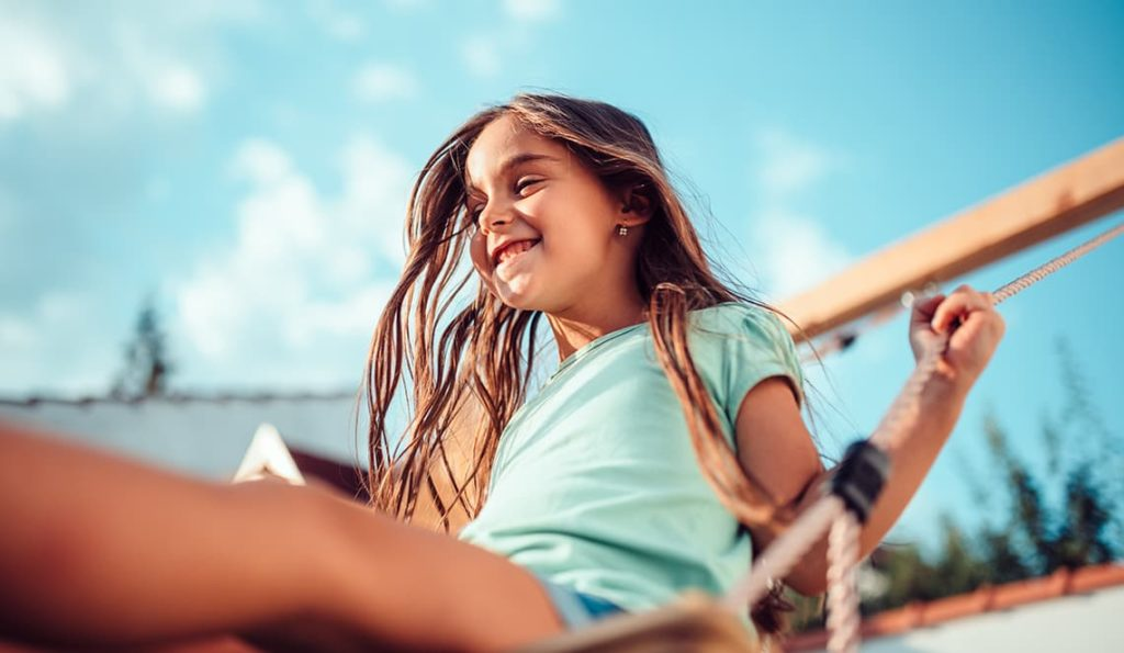 Portrait of a happy little girl wearing green shirt sitting on a swing and smiling