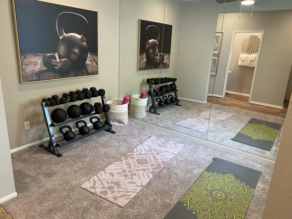 Rack of weights and yoga mats inside Verbena model home