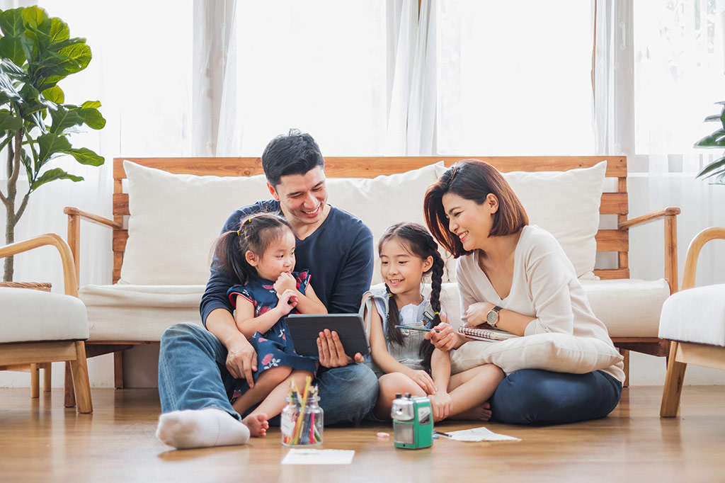 family gathered watching a tablet