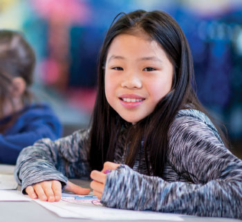 school girl smiling and coloring